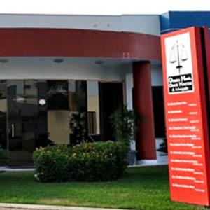 A placa vermelha fixada no jardim destaca a fachada do escritório de Porto Velho/RO.