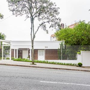 Localizada no coração do Centro Cívico em Curitiba, próximo ao TJ/PR, a fachada da banca de estilo inglês, com suas colunas e linhas retas, harmoniza-se com o jardim frontal.