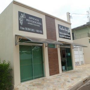 A calçada de pedras se contrapõe à faixa amadeirada decorativa da fachada do escritório de Junqueirópolis/SP.