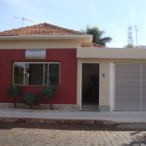 O vermelho queimado e o tom pastel harmonizam a fachada do escritório da pequena Nuporanga/SP.