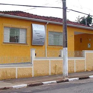 A parede mostarda sustenta o painel prateado de identificação da banca mineira de Guaxupé/MG.