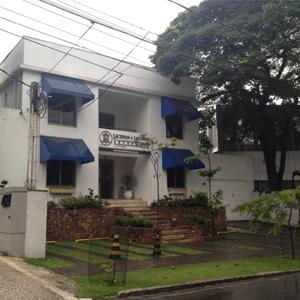 Ao lado de uma frondosa árvore, o escritório de São Paulo/SP tem em sua fachada uma mureta de pedras cheia de volumosos arbustos e flores coloridas.