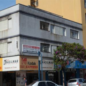 Da avenida movimentada no centro de Poços de Caldas/MG é possível notar em prédio comercial a placa do escritório de advocacia.