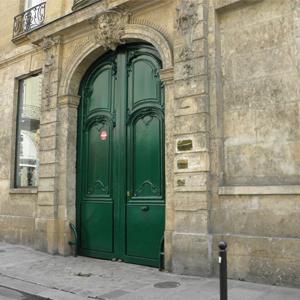 A suntuosa porta verde da banca de Paris/França é ornamentada com linhas que remetem à época antiga.