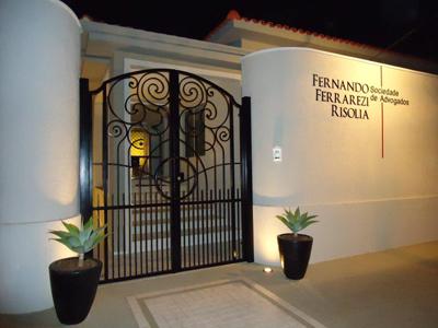 O letreiro da banca se destaca juntamente com as luzes e o portão do escritório em São Paulo/SP.