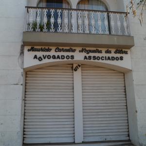 As letras cursivas em preto destacam na fachada toda branca do escritório mineiro de Poços de Caldas/MG.