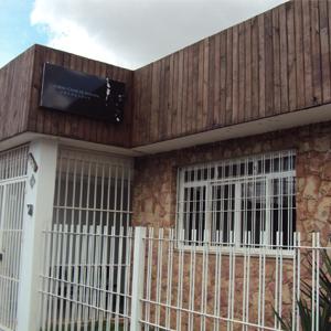 As ripas de madeira no alto da fachada do escritório de Franca/SP contrastam com a parede de pedras.