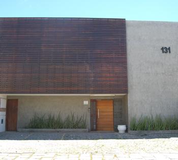 As ripas de madeira no alto da fachada contrastam com a parede de concreto e as plantas harmonizam a entrada do escritório em Salvador/BA.