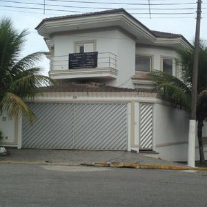 A casa marcada por uma arquitetura recortada abriga o escritório do Guarujá/SP.