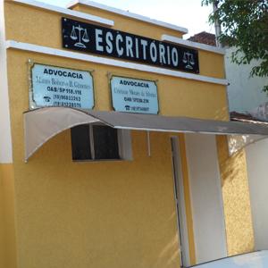 Na parede com efeito grafiato, as placas de vidro indicam os profissionais do escritório de Pacaembu, interior paulista.