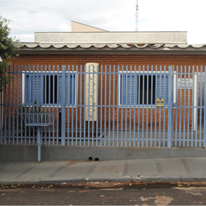 Por entre as grades cinza, a placa mostra que a casa de tijolos à vista em Cassilândia/MS é um escritório de advocacia.