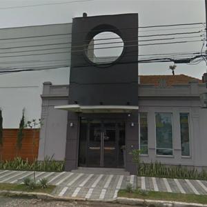Com uma arquitetura diferenciada, o escritório sulista de Pelotas é circundado por um verde canteiro e uma calçada de faixas brancas e cinzas.